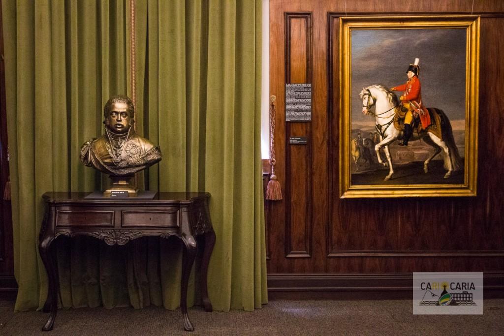 Decoração antiga, com muitos quadros, bustos e parede de madeira, com móveis antigos